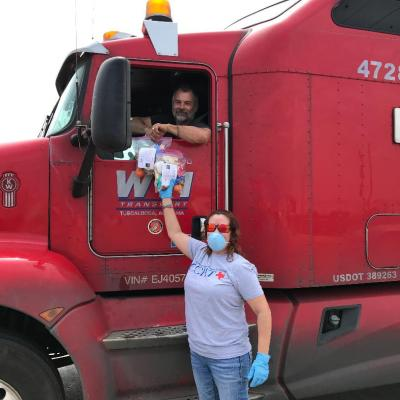 Volunteer Iris Ortiz handing out snack bags to one of the many truckers working so hard to keep our stores supplied!
