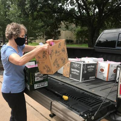 Volunteer Marcia from Tallowood Baptist Church Harvesters Class helps load snack bags prepared by their class