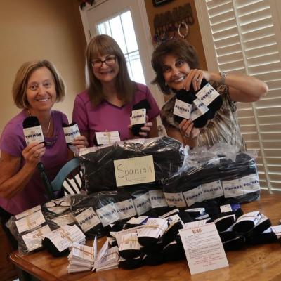 Volunteers attach trafficking info to socks for distribution to at-risk individuals
